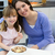 child eating cereals with her mom in the kitchen stock photo © nenetus