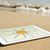 sun drawn in a tablet in the sand of a beach stock photo © nito
