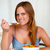 Relaxed pretty young girl eating breakfast stock photo © pablocalvog