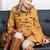 vrouw · bruin · jas · vergadering · sofa - stockfoto © phbcz