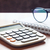calculator with eyeglasses on wooden table stock photo © punsayaporn