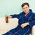 young man drinks beer in dressing gown on sofa stock photo © pzaxe