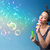 pretty lady blowing colorful bubbles on blue background stock photo © ra2studio