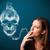 young woman smoking dangerous cigarette with toxic skull smoke stock photo © ra2studio