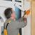 worker installing wooden door using polyurethane foam stock photo © simazoran