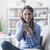 笑顔の女性 · 座って · ソファ · スマートフォン · 電話 · 幸せ - ストックフォト © stokkete