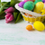 easter yellow wicker basket with multicolored eggs stock photo © tasipas