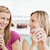 Delighted female friends holding a cup of coffee at home in the living-room stock photo © wavebreak_media