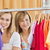 Beautiful female friends doing shopping choosing shirts in a clothes store stock photo © wavebreak_media