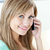 Happy young woman talking on phone smiling at the camera in the kitchen at home stock photo © wavebreak_media