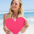 smiling blonde showing pink heart on the beach stock photo © wavebreak_media