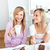 Happy female friends eating a chocolate cake and drinking in the kitchen at home stock photo © wavebreak_media
