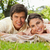 Man and a woman lying prone together on a blanket in the grass while smiling stock photo © wavebreak_media