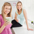Portrait of two happy women holding cups of coffee at home in the kitchen stock photo © wavebreak_media