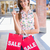 portrait of smiling woman with sale shopping bags showing credit stock photo © wavebreak_media