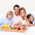 Smiling family having breakfast sitting on bed at home stock photo © wavebreak_media