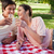Two friends smiling and raising their glasses in toast while lying on a red and white picnic basket stock photo © wavebreak_media