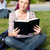 Bright female student reading a book sitting on the grass in her university campus stock photo © wavebreak_media