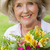 close up of a smiling mature woman holding flowers at park stock photo © wavebreak_media