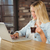 smiling woman drinking coffee and typing on laptop stock photo © wavebreak_media