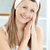 Smiling young woman putting cream on her face in the bathroom at home stock photo © wavebreak_media