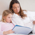 cute girl reading a book with her mother in a bedroom stock photo © wavebreak_media
