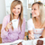 Joyful female friends eating a chocolate cake and drinking in the kitchen at home  stock photo © wavebreak_media