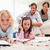 cute siblings drawing while their parents are in the background in a living room stock photo © wavebreak_media