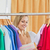 Cute young woman holding a colorful shirt in a clothes store stock photo © wavebreak_media