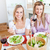 Pretty women eating a salad and drinking wine in the kitchen at home stock photo © wavebreak_media