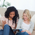 two women are sitting down on the ground reading a magazine stock photo © wavebreak_media