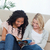 two smiling women are sitting on the ground leaning against a couch reading a magazine stock photo © wavebreak_media