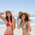 Happy young women sunbathing while standing in front of the sea side by side stock photo © wavebreak_media