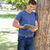 male student leaning against a tree while using a touch pad in a park stock photo © wavebreak_media