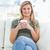 erschossen · Frau · lächelnd · Sitzung · Couch · Beine · gekreuzt · halten - stock foto © wavebreak_media