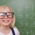 Smart schoolgirl posing in front of a blackboard in a classroom stock photo © wavebreak_media