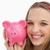 Close-up of a young woman holding a piggy-bank against white background stock photo © wavebreak_media