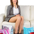 smiling young woman sitting on couch with shopping bags stock photo © wavebreak_media