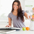 beautiful woman consulting a notebook while filling a blender with fruits in the kitchen stock photo © wavebreak_media