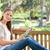 side view of a young woman with a tablet computer on a park bench stock photo © wavebreak_media