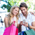 smiling couple with shopping bags sitting and using smartphone stock photo © wavebreak_media