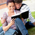 Serious couple of students reading a book sitting on grass at their campus university stock photo © wavebreak_media