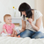 Charming brunette female showing a feeding bottle to her baby while sitting on a bed in her appartme stock photo © wavebreak_media