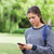 Young calm girl using her mobile phone to send a text while standing in a park stock photo © wavebreak_media