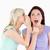 Portrait of a blond woman telling her friend a secret in a studio stock photo © wavebreak_media