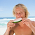 Young man eating a piece of watermelon in front of the sea stock photo © wavebreak_media