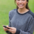 Young smiling adult looking straight at the camera while using her mobile phone stock photo © wavebreak_media