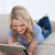 A young smiling woman lying on a couch is using her tablet stock photo © wavebreak_media