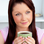 Positive woman holding a cup of coffee at home in the living-room stock photo © wavebreak_media