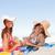 mulheres · jovens · praia · toalhas · olhando · câmera · smiles - foto stock © wavebreak_media